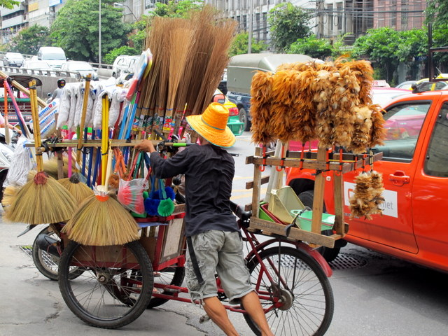 Bangkok Broom Peddler amid highrises and traffic