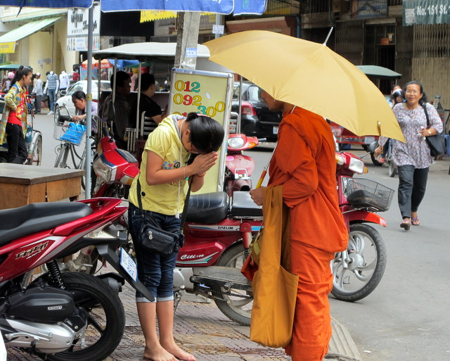 Monks gives blessing to a lady at the morning market