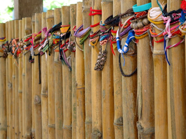 Prayer bracelets hung on the fence surrounding the mass grave of women & children