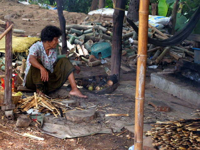 Woman cutting bamboo and making sticky rice