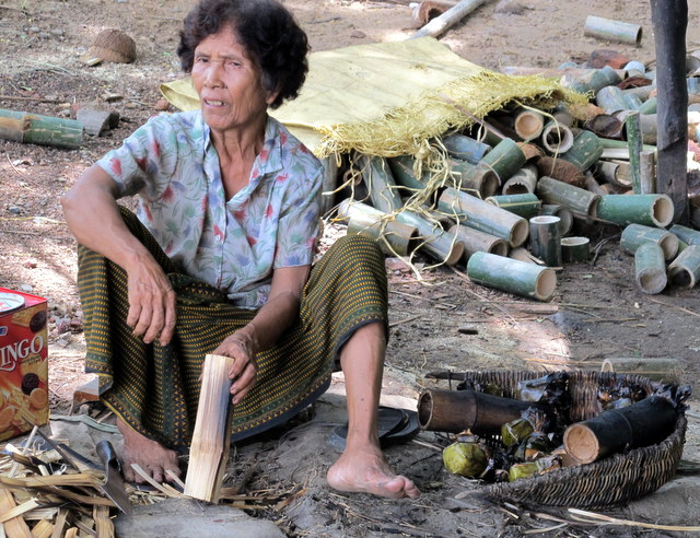 Outside Battambang woman cuts bamboo to be filled with sticky rice