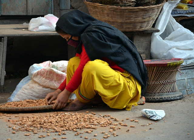 Girl cleaning nuts on the steet in Kathmandu, Nepal