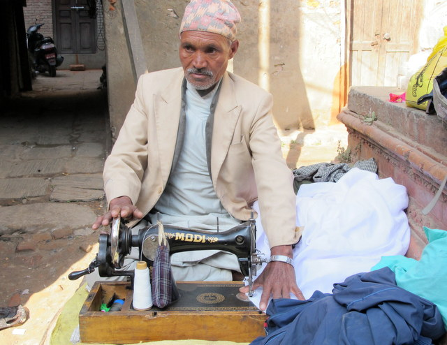 An old tailor with his hand turned sewing machine on the streets of Kathmandu, Nepal